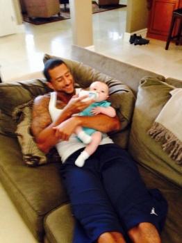 Colin Kaepernick feeding a baby